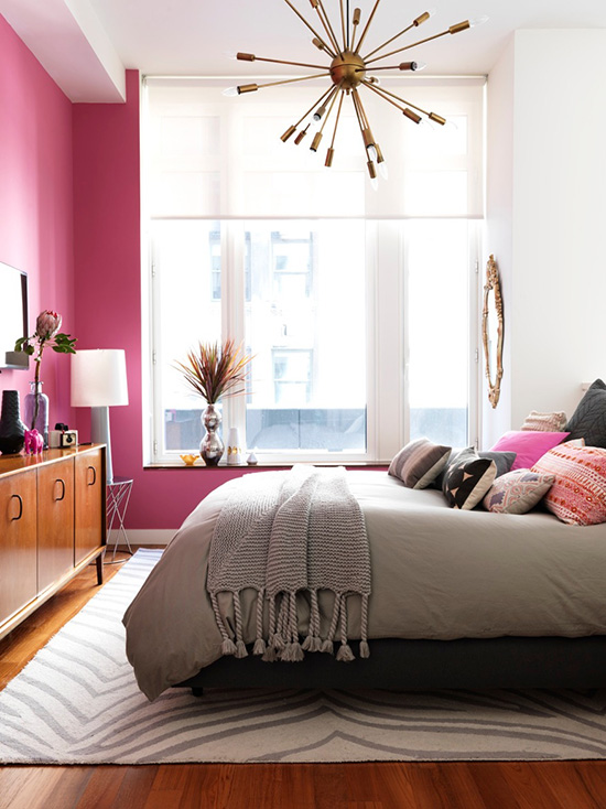 Raspberry pink walls in a bright, modern bedroom.