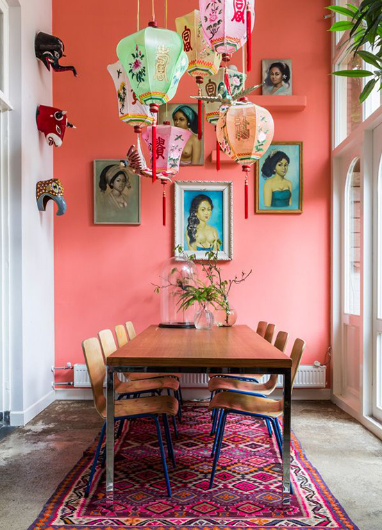 Salmon pink feature wall in a dining room with an amazing overhead fixture and that gallery wall!