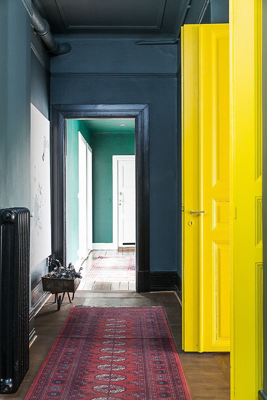 An incredible hallway with dark blue walls and yellow doors. Spotted on SoFreshAndSoChic.com #sofreshandsochic #darkbluewalls #yllowdoors #traditionalrunner #boldcolours