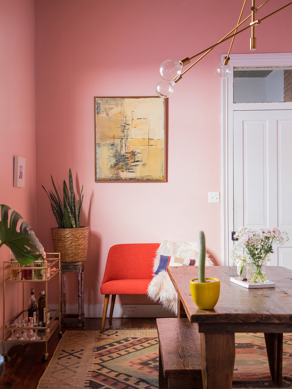 So Fresh & So Chic // Pink and Red Interiors // Pink dining room walls with red accent sofa
