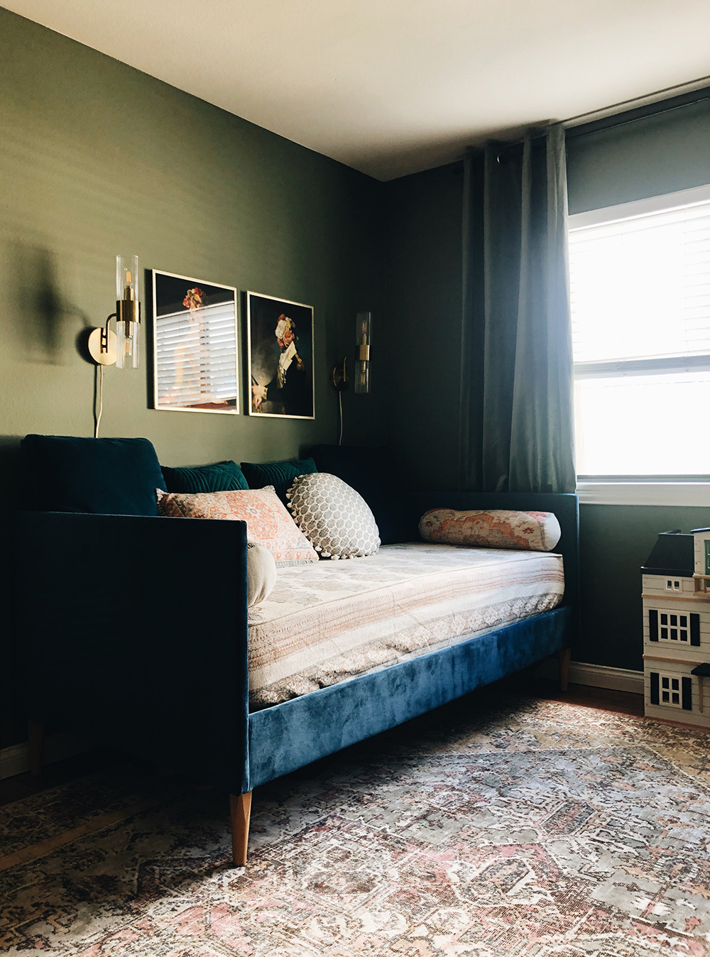 Navy blue velvet daybed and vintage style portraits